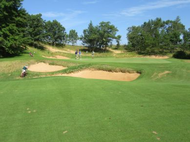 Teddy Greenstein high-fiving Steve Schapiro after his first eagle on the par four 9th at Sand Valley GC
